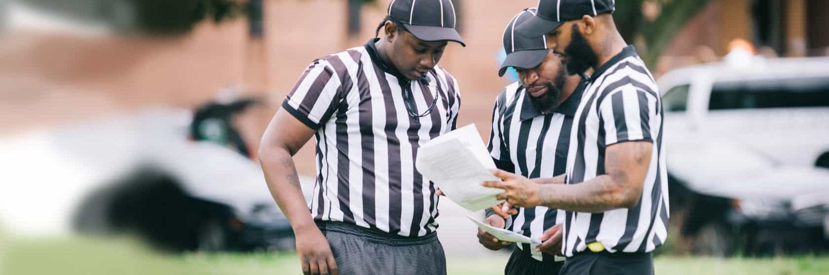 Three flag football referees reviewing game rules